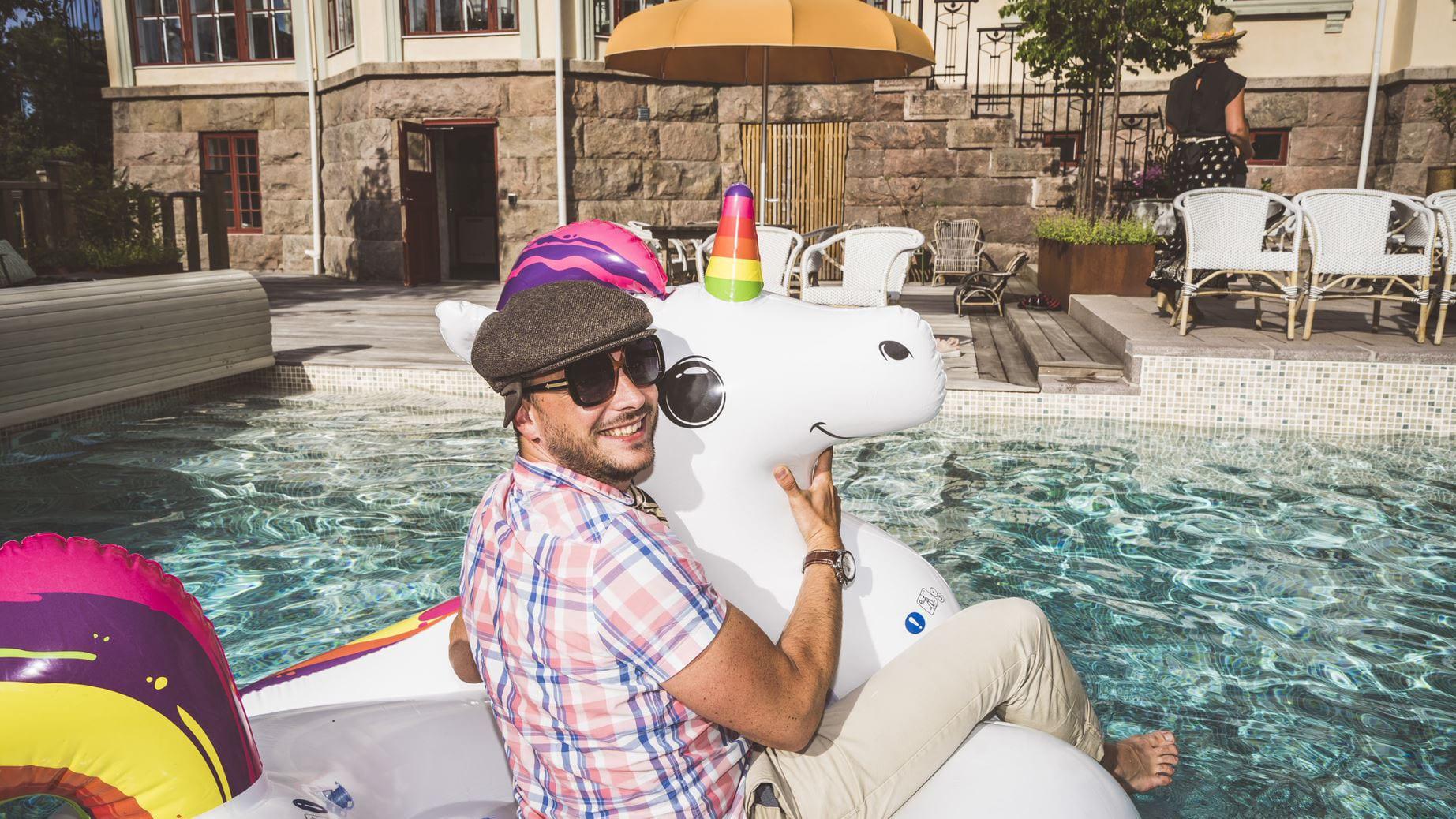 Man som rider på en uppblåsbar enhörning i poolen vid Villa Strömsfors